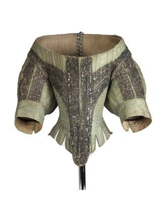 A woman's bodice made from green silk, lined with linen, and trimmed with silver bobbin lace and silver alloy spangles. It is heavily boned with whale bone. It has a low wide neckline and full short sleeves finished with a cuff. It has tabs at the waist with longer oval shaped tab at the centre front. It fastens with lacing at the back. The silk is Italian, probably from the first quarter of the Seventeenth century.
