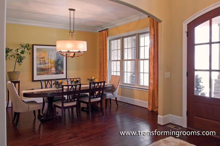 Dark traditional furniture are updated through window treatments, art, and the centerpiece. The ivory host and hostess chair are a nice contrast.