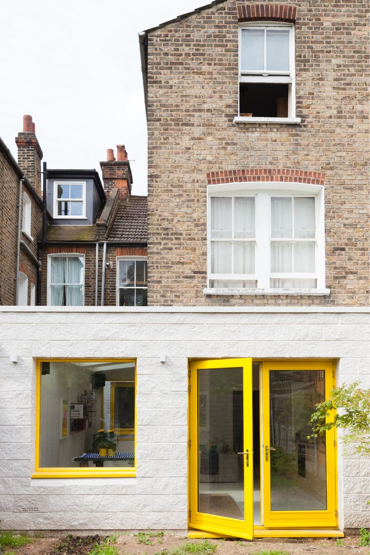 white rear extension, textured Forticrete blockwork, yellow timber framed doors, yellow timber frame fixed window, brass ironmongery