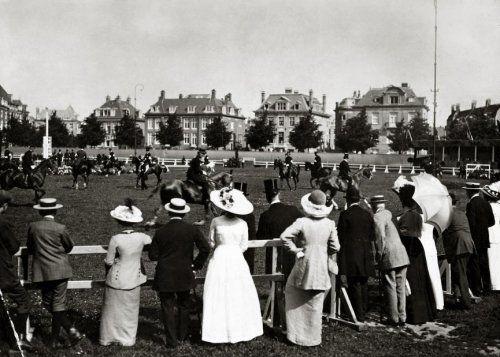 Gadegeslagen door toeschouwers in zomerse kleding met strohoeden en parasols, rijden de deelnemers aan het Concours Hippique in Amsterdam in 1913  zich warm op de terreinen van de Amsterdamsche IJsclub.