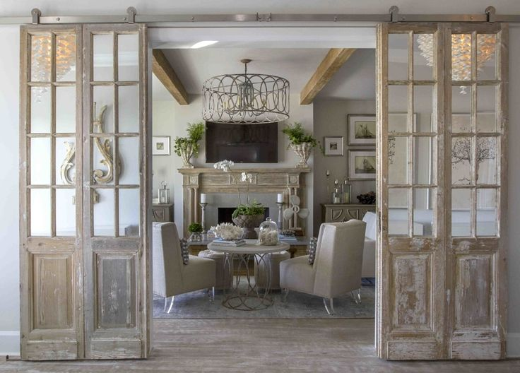 """""""I ran across a pair of old French doors that were fabulous and I knew immediately we had to incorporate into the design somewhere,"""" says Carol. """"We decided to have them hung on a stainless sliding bar to frame out the living room."""" This antique mantel originally was housed in the Yale library back in the 1900s."""