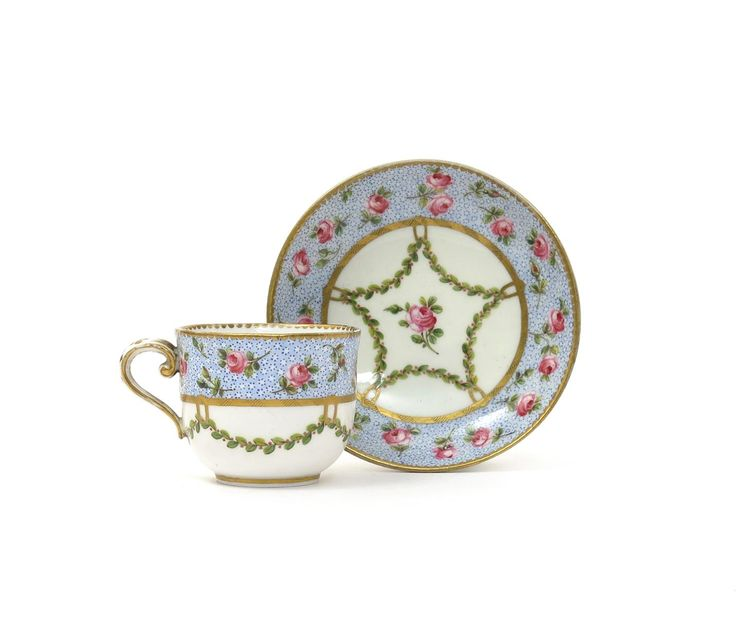 A rare Sèvres small cup and saucer date code for 1768, painted with sprays of pink roses reserved on a blue oeil de perdrix ground, with suspended berried swags, the saucer unusually incised 'pate no. 43', blue interlaced LL mark and painter's initials SC.