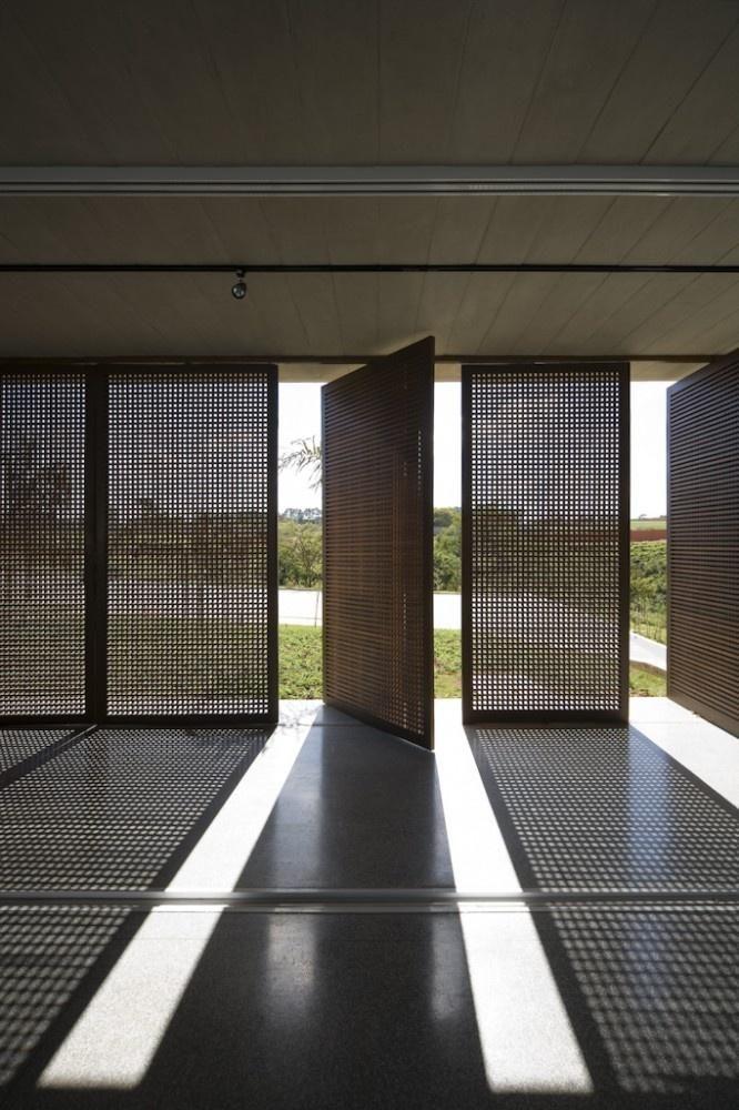 As portas pivotantes perfuradas criam um desenho devido à incidência da iluminação natural no chão.  Fotografia: http://www.decorfacil.com/portas-pivotantes/