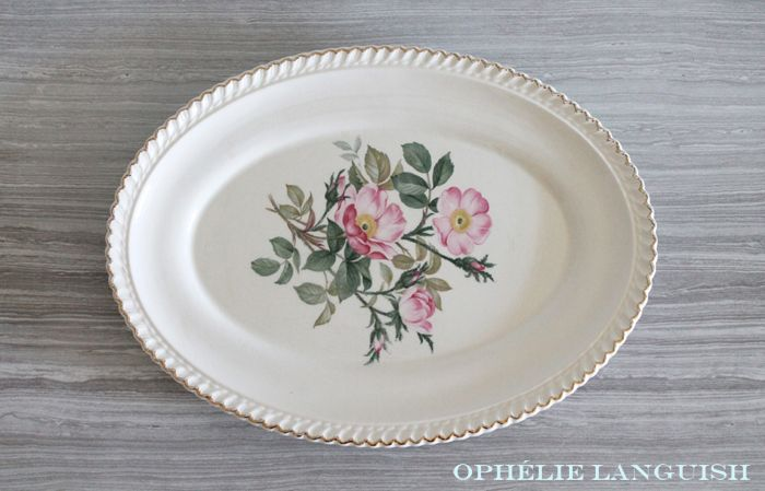 Beautiful cream coloured oval platter featuring a pink wild rose centre motif. Fluted edges and 22 KT gold trim. A very charming addition to a shabby chic dinner or table setting.