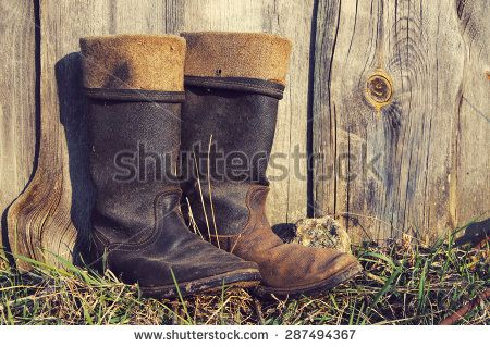 Old men's boots on a wooden impressive background. Old worn footwear. - stock photo
