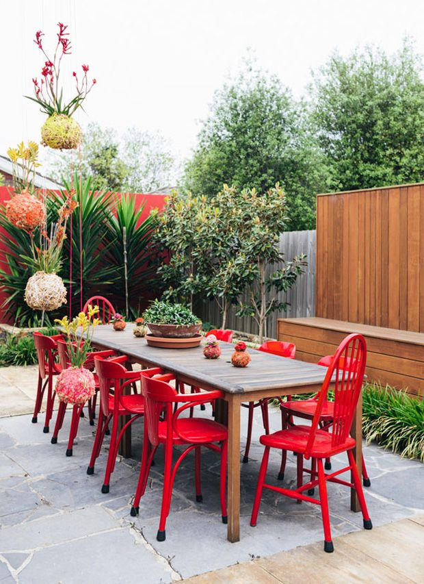 wall with built in bench, hanging plants, colorful wooden chairs with rubber feet covers for wet weather