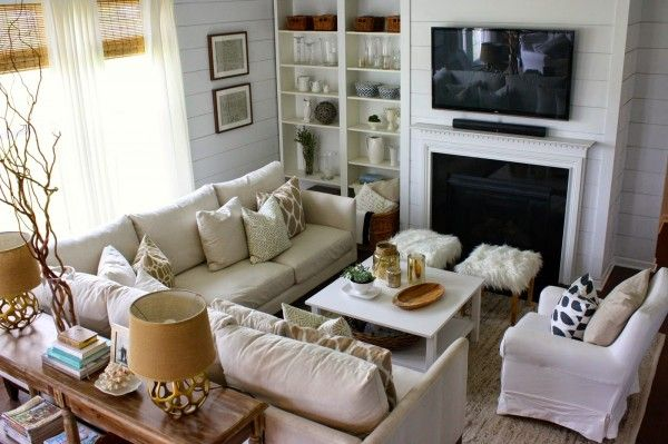 Great furniture layout - love the sectional sofa and the console table with the two little ottomans. Small living room with fireplace