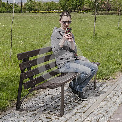 Young woman on the bench in new park in old Sanatorium Marconi in Busko-Zdrój in Poland. Europe.