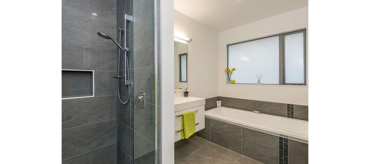 modern bathroom, grey tiles, green towels, white walls
