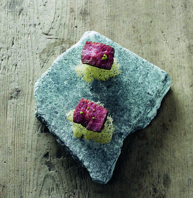 A Recipe by Magnus Nilsson | FOUR Magazine.  tiny slice of top blade from a retired dairy cow, dry aged for nine months, crispy reindeer lichen, fermented green gooseberries & fennel salt