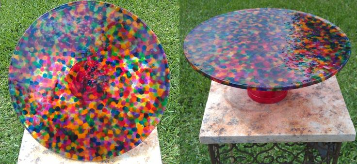 "Stained Glass Cake Stand.  Fill tof a 12"" cake pan with CHEAP, plastic, transparent pony beads. Baked them in a 425 degree oven for 30-40 minutes until all the beads had melted. Let the pan cool for 20 minutes, then flip the melted bead 'plate' out  Finally, I glued it to a dollar store candle stick and, presto! Cake stand!"