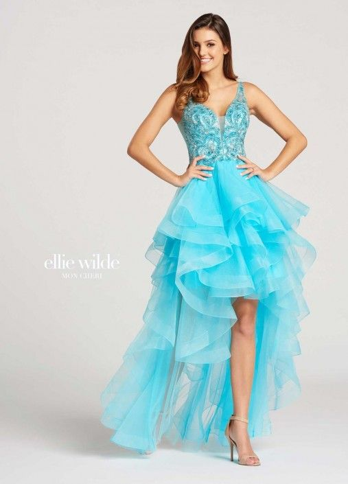 Style EW118093 from Ellie Wilde for Mon Cheri is a formal sleeveless sheer V-neck Tulle High-Low Prom gown with a V back, beaded bodice, and ruffled tiered skirt.