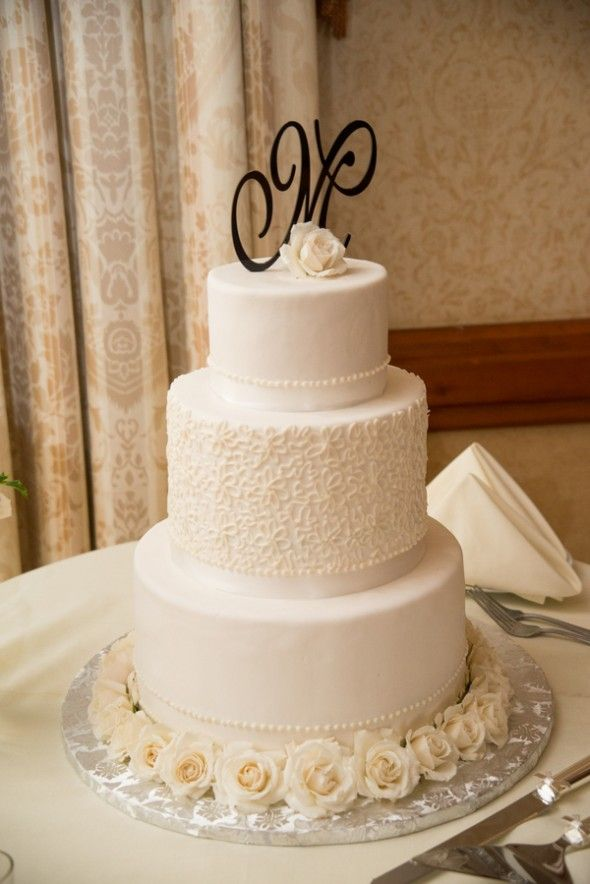 A Lovely White Wedding Cake With Monogrammed Initial Topper