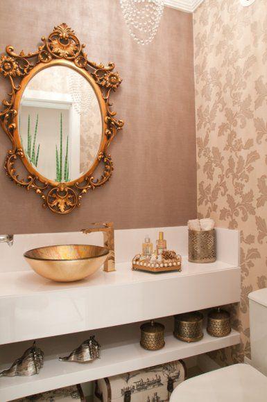 No lavabo, a bancada em laca high gloss branca realça os papéis de parede aplicados no espaço e valoriza a cuba e o espelho de tom dourado.