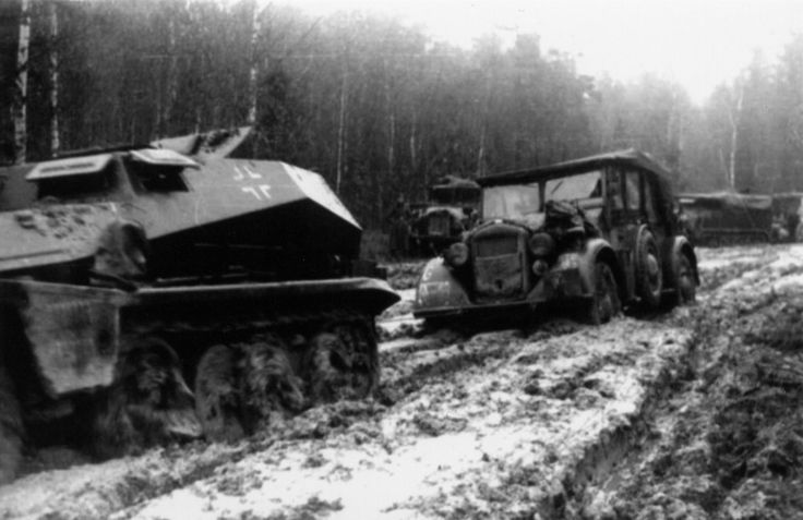 A SdKfz 251 and a officer staff car finding travel difficult in thick muddy roads operating in Russia