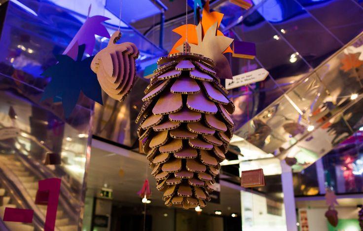 Decoración centro comercial Pedralbes Centre Barcelona. Motivos otoñales hechos con cartón y papel: piñas, hojas, bellotas.