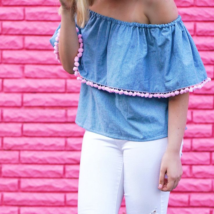 Our chambray pom pom off the shoulder top is unique and sassy. Chambray fabric and pink jumbo sized pom poms with elastic across the top to keep the shirt in place. The shirt is made from an opaque fa