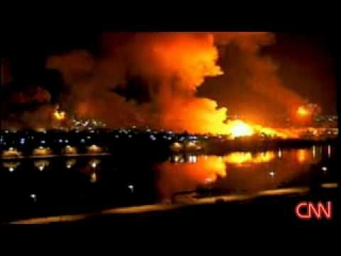 "The 2003 night-bombing of Baghdad, as aired live on CNN. The home audience is given a sanitized view of warfare, as American bombs lay waste to the city. The ""Shock and Awe"" of the mission's title is as much directed to the enemy as it is to the American people. That is, seeing these images is intended to impress, and to give the impression of a targeted and necessary attack, one that is minimizing civilian casualties and ""getting the job done."""
