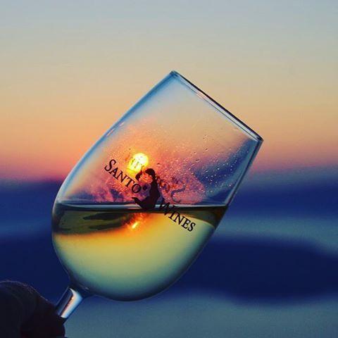 A sip of #Santorini's #sunset! #wine #SantoWines Photo credits: @liliaworldtravel