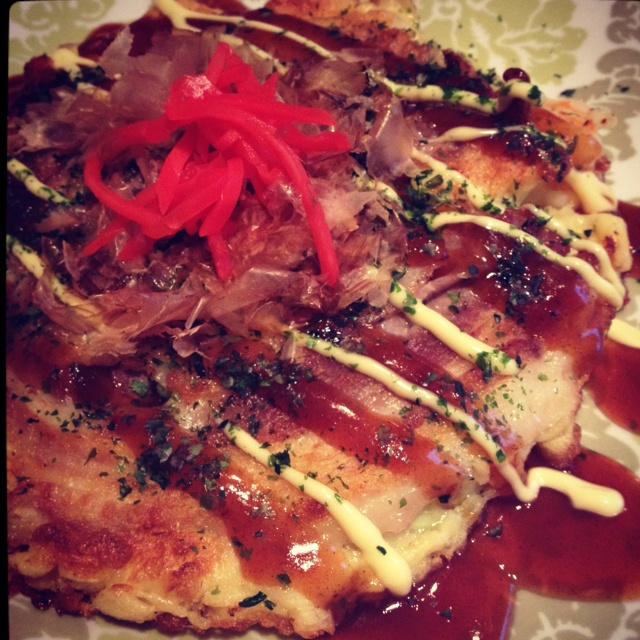 """is a Japanese savoury pancake containing a variety of ingredients. The name is derived from the word okonomi, meaning """"what you like"""" or """"what you want"""", and yaki meaning """"grilled"""" or """"cooked"""""""