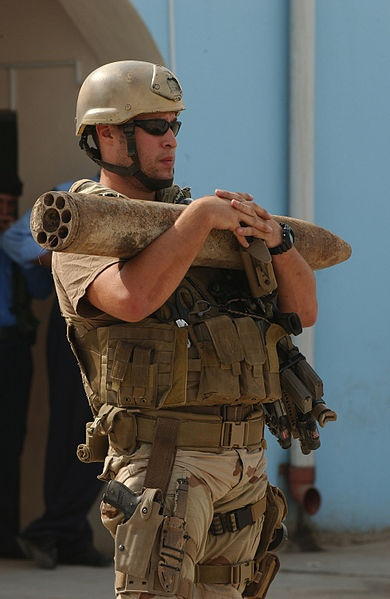 U.S. Navy Petty Officer 2nd Class Derek Brundage carries one of several Katiush Rockets out of the Iraqi police headquarters in Ad Diwaniyah, Iraq, Oct. 30, 2006, for transport to Camp Echo, Iraq. Brundage is an explosive ordnance disposal tecnician assigned to the U.S. Navy EOD Mobile Unit 3, which responded to the Iraqi police headquarters to recover a cache of explosives found by policemen during a checkpoint vehicle search. U.S. Air Force photo by Tech. Sgt. Dawn M. Price