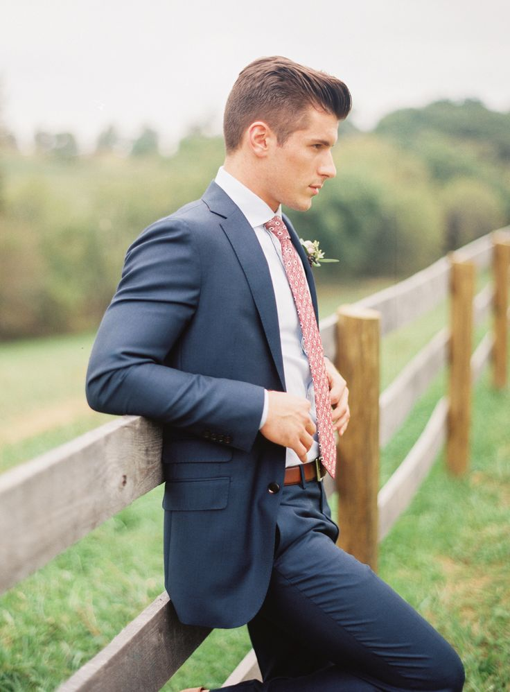 Groom style: Navy blue suit with pink patterned tie. Image by Jodi Miller Photography.