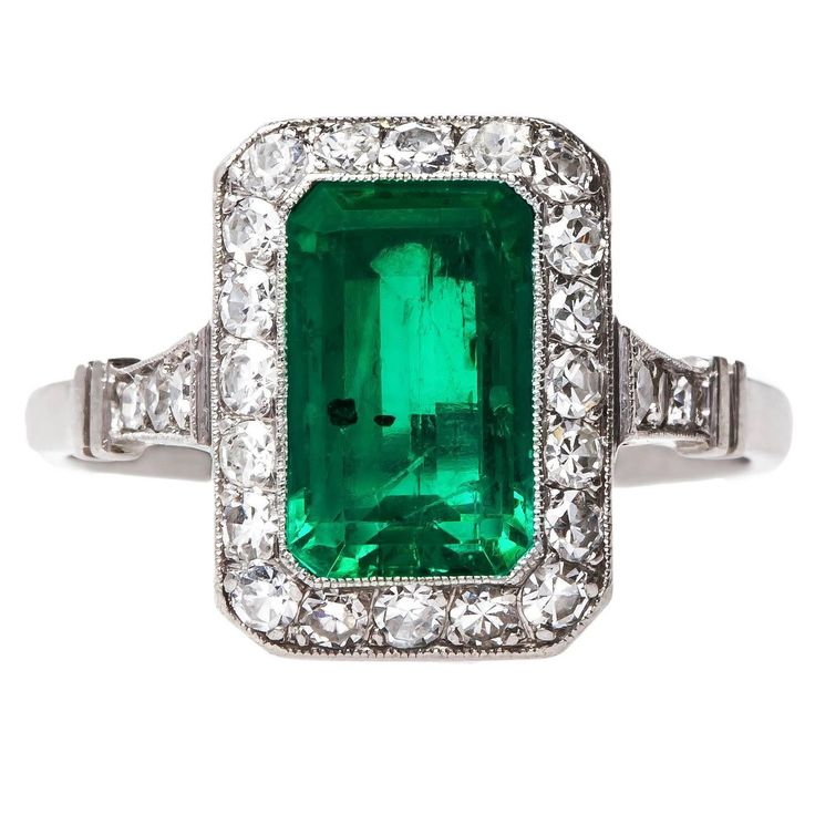 Quintessential Art Deco Colombian Emerald Diamond platinum Engagement Ring...a bezel set 1.85ct Rectangular Step Cut emerald... The ring's center emerald has an amazing hematite inclusion that reflects a stunning metallic color inside the stone and makes it incredibly unique. Avalon Park is further accented by twenty-six Single Cut diamonds framing the center stone and lining the shoulders of the ring, totaling approximately 0.65ct. c 1930