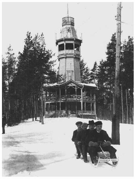 Kelkkailijoita Pyynikillä, taustalla Pyynikin vanha näkötorni 1912 -1913  (Tampereen museotoimen kuva-arkisto, kuvaaja tuntematon)