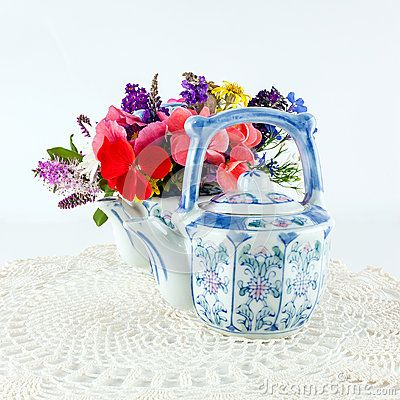Colorful painted teapots with garden flowers on white lacy doily.