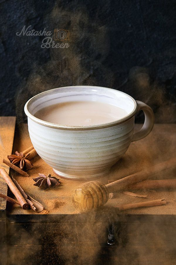 Masala Chai - White ceramic cup of hot masala chai, served with honey on honey…