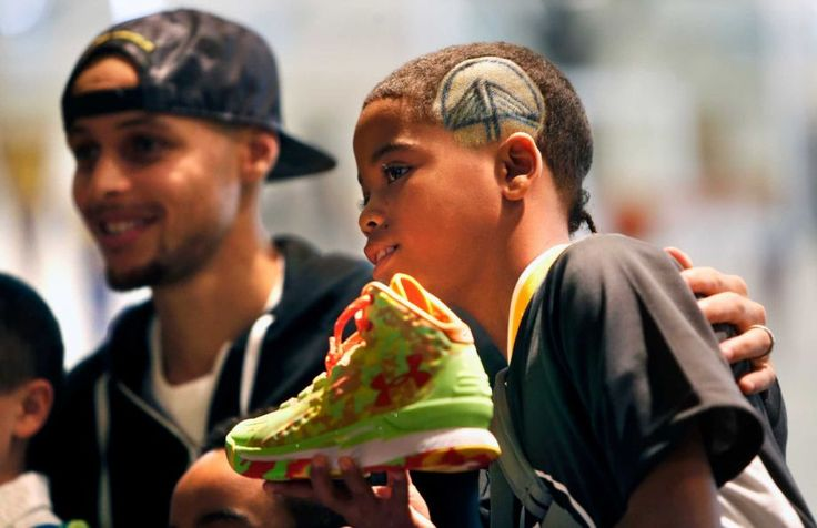 The Warriors' Stephen Curry poses with Make-A-Wish recipient Cash Banks, 10, of San Francisco after the unveiling of Curry's new Under Armour shoe line at St. Joseph Notre Dame High School in Alameda on Thursday. Photo: Scott Strazzante / The Chronicle / ONLINE_YES
