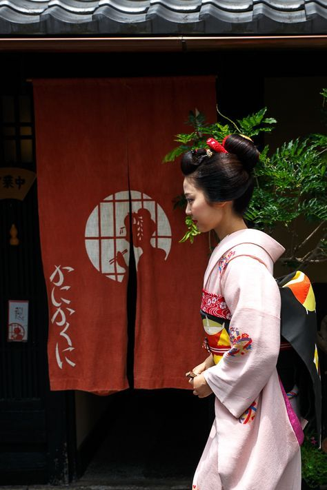 Japanese lady walking past the curtain/noren of a restaurant