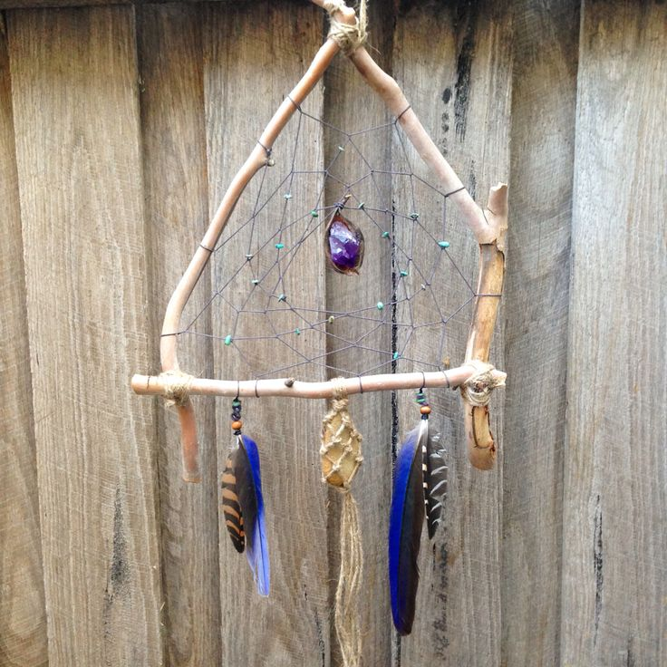Wooden dreamcatcher with eucalypt branches, rosella & quail feathers, African turquoise & amethyst beads and an amethyst point & seedpod centrepiece #amethystpoint #handmade #handicraft #dreamcatcher #feathers #beadwork #artwork #africanturquoise #seedpods