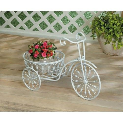 """Old world charm will bloom anywhere this three-wheeled bicycle goes. Made from iron and finished in white, this vintage-style bicycle plant holder has a generous basket that's ready to seat your potted greenery. Display it indoors or outside. Weight 3.4 pounds Dimensions 20.8"""" x 10"""" x 14.1"""" UPC Number: 849179031770 Material(s): IRON"""