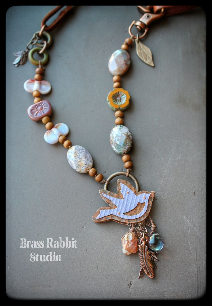 Boho style mixed media necklace with beautiful copper and recycled laminant sparrow pendant, hand forged by La Bella Joya, faceted ocean jasper, lampwork wing dings by Genea, lampwork flower tabs by Sue Beads, table cut Czech glass flower, sandalwood rounds, lampwork rings by Out West, copper fringe chain, copper feather charm, mystic quartz and rainbow florite wirewrapped charms, bronze leaf charm by Lesley Watt, copper swivel base lobster clasp, and soft Italian leather lace!