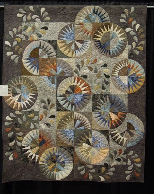 Rob's Quilt by Kathy Martin -- Kathy made this quilt for her son Rob, using the New York Beauty pattern of points arrayed in circular arcs. Her skillful use of light and medium shades of neutral hues gives this quilt interesting depth and shadows. Notice how Kathy has appliqued sprays of leaves that follow the circular shape of the blocks for extra visual interest.