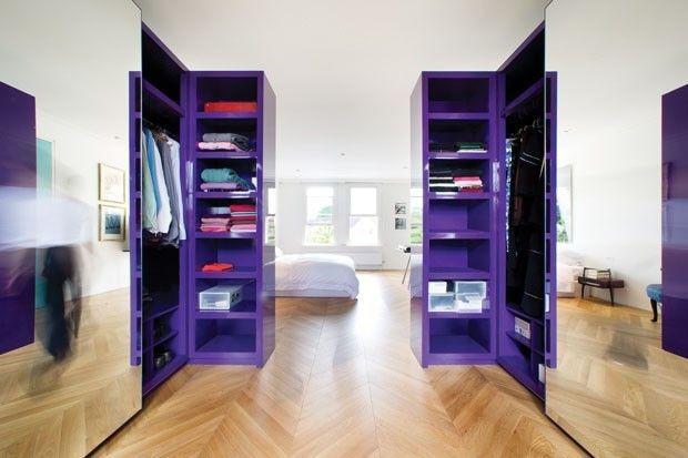 Closet poderoso! O armário laqueado roxo criou um volume impactante neste quarto branco com piso de taco em formato espinha de peixe. O cubo cria uma subdivisão no ambiente sem precisar de paredes.