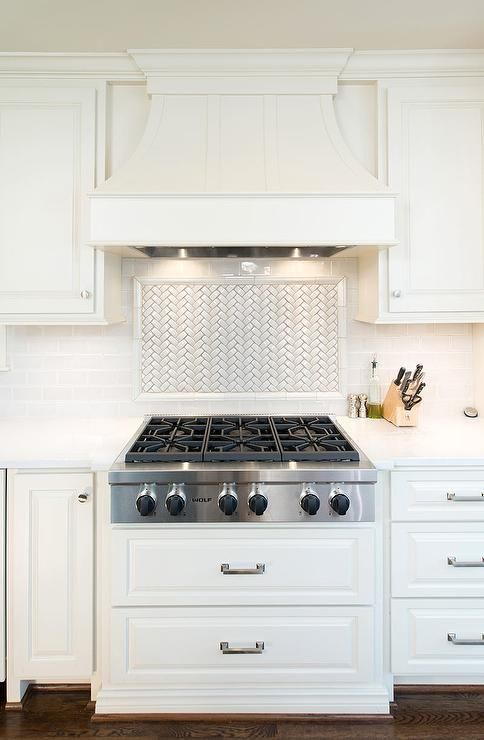 A white paneled French kitchen hood stands over a white herringbone cooktop backsplash and an integrated Wolf cooktop situated above stacked pot and pan drawers.
