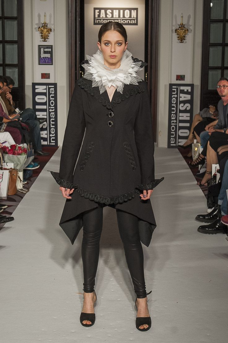 "Lenie Boya ""Dramatique"" Collection at London Fashion Week S/S 2016 Haute Couture. Black angular coat with lace crochet details, high collar and white pleated ruff collar."