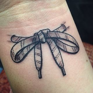 This delicate bow. | 15 Badass Hockey Tattoos That Prove Ice And Ink Belong Together