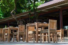 Restaurante al aire libre con sillas y mesas de madera Foto de archivo