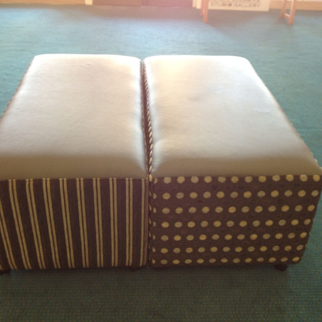 The finished ottoman's in grey leather tops and matching dots and striped fabric.