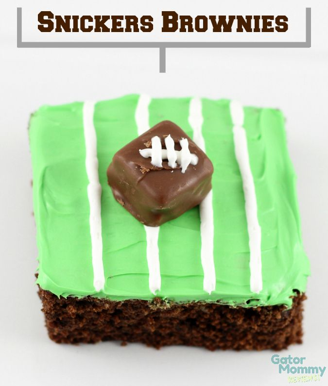 Snickers Brownies are the ultimate football party dessert. The combination of Snickers candy bars and brownies is irresistible to guests. Each brownie is decorated as a football field with green icing with white icing as the field lines. Then topped with decorated Snickers mini as footballs.