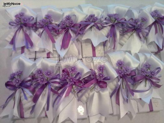 http://www.lemienozze.it/operatori-matrimonio/bomboniere/confetti-bomboniere-matrimonio-milano/media/foto/10?play=1 Sacchetti in raso e fiocchetti viola per il confetti delle bomboniere matrimonio
