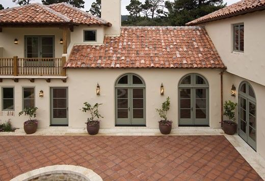 Exterior Of A SPANISH STYLE LUXURY HOME With Stucco Walls A Red Tile Roof And