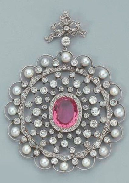 A BELLE EPOQUE DIAMOND, PINK TOPAZ AND PEARL PENDANT, CIRCA 1910. The oval mixed-cut topaz of violet pink tone set within a trellis work frame surrounded by a pearl and diamond-set border, from a similarly-set bow surmount, restored. #BelleÉpoque #pendant