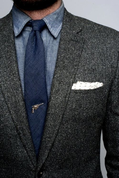 Grey coat, blue skinny tie, denim dress shirt, revolver tie tack