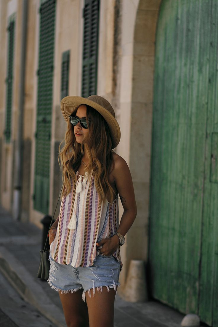 Desi is wearing: striped top with tassels, ripped cut-off denim shorts, Céline trio bag, straw hat - summer holiday look in Santanyí - teetharejade.com