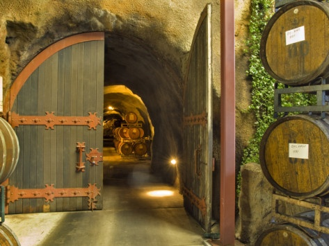 Oak Barrels Stacked Outside of Open Door To Aging Caves at Ironstone Winery, California