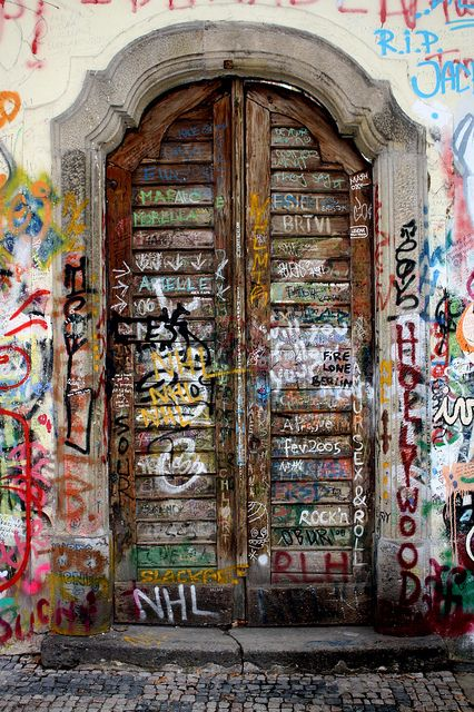 Door in the Lennon Wall  A door in the Lennon Wall in Prague, Czech Republic covered with writing and graffiti. This wall was used as a form of free speech during a time when free speech was suppressed by a communist government.